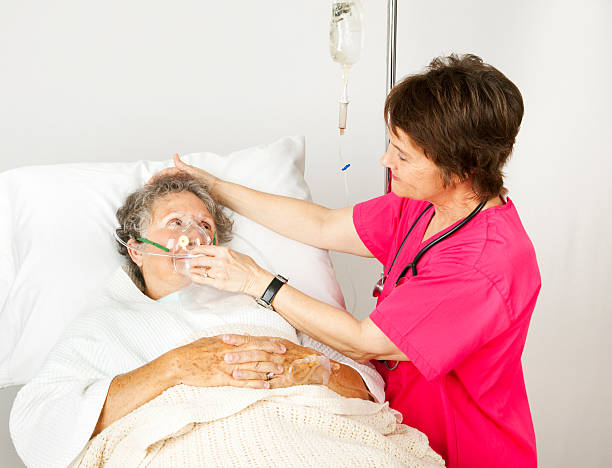 Oxygen Mask in the Hospital Hospital nurse helps a senior woman breath through an oxygen mask. oxygen mask stock pictures, royalty-free photos & images