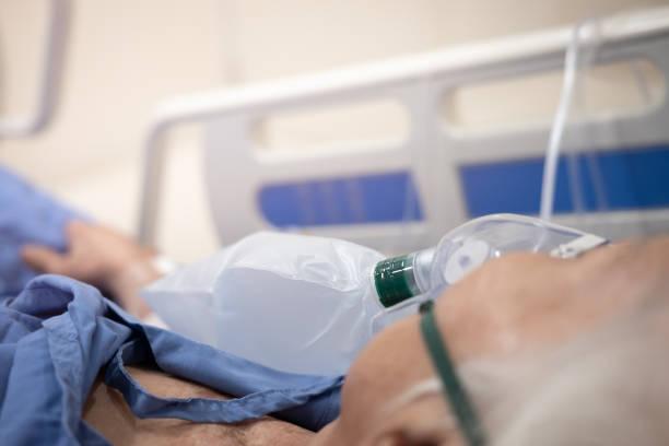 syrgasmask på patientens ansikte på sjukhussängen - kvinna ventilationssystem bildbanksfoton och bilder
