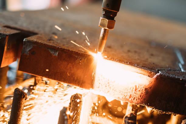 Oxygen torch cuts steel sheet. CNC gas cutting machine. Bright sparks stock photo