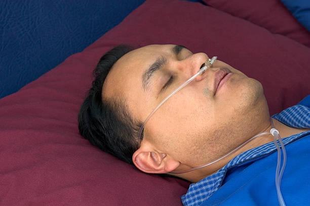 oxygen user hispanic man sleeping using oxygen oxygen tube stock pictures, royalty-free photos & images