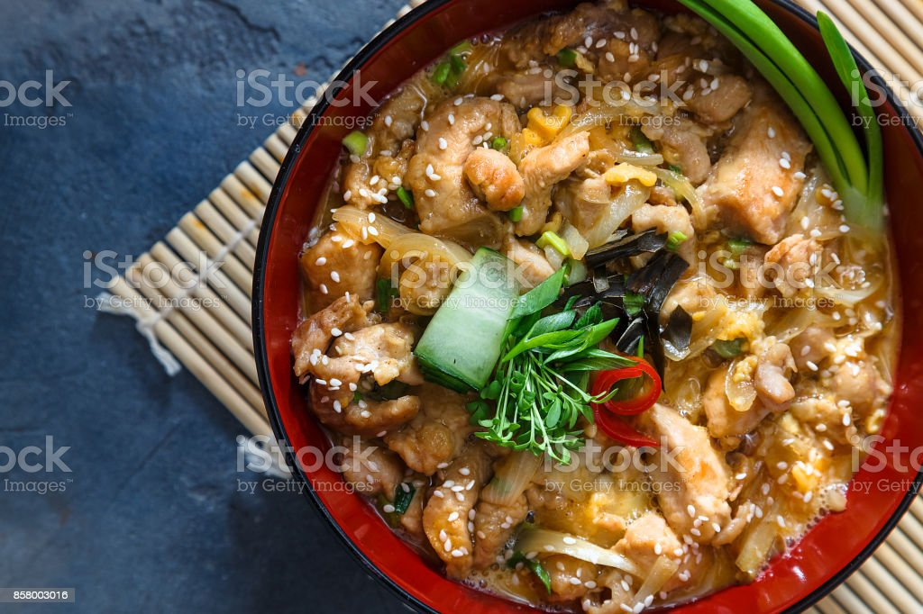 Oyakodon Japanese rice on topped with chicken, egg, onion, and seaweed in ceramic rice bowl. stock photo