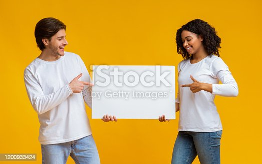 1159989540 istock photo oyful interracial couple holding and pointing at blank advertisement placard 1200933424