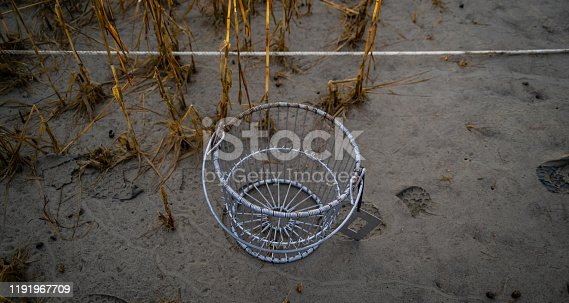 A wire basket with a measuring tool and boot tracks in the sand.
