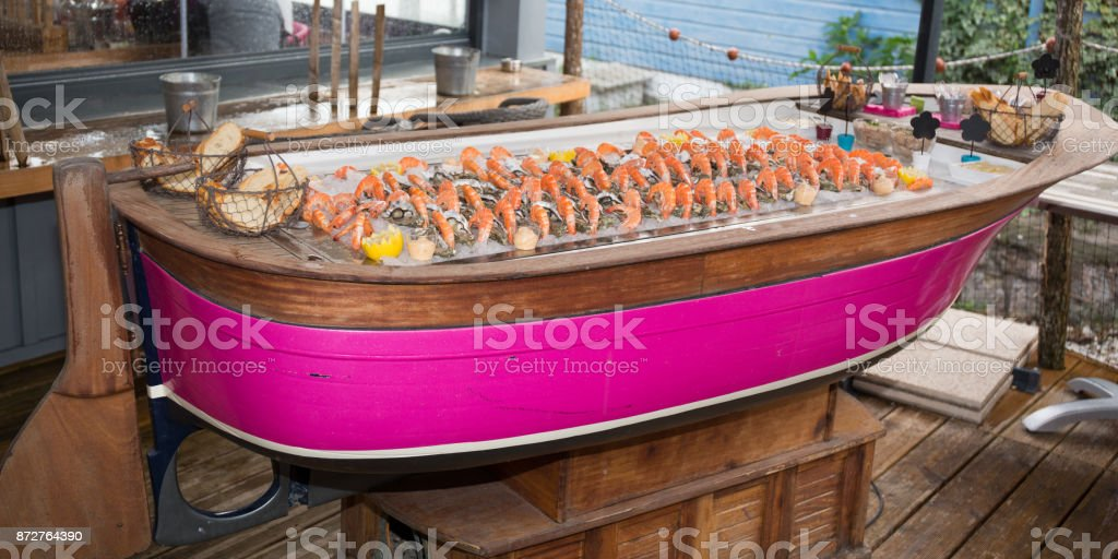 Oyster on ice with lemon and shrimps stock photo