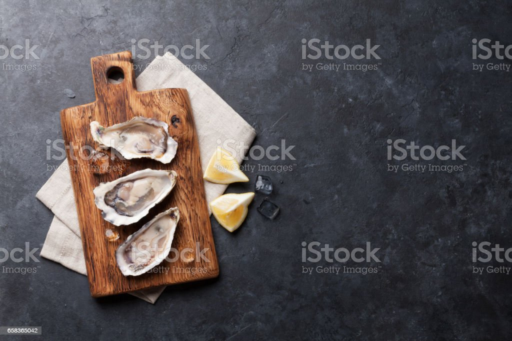 Oysters and lemon over ice stock photo