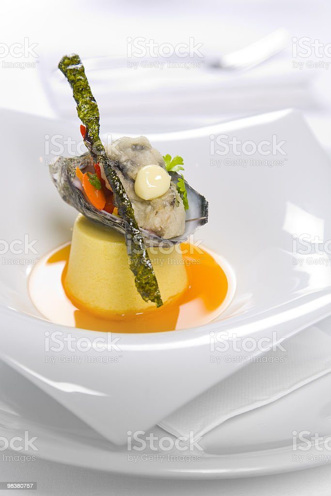 Oysters Kilpatrick served on designer plate in restaurant royalty-free stock photo