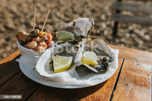 Assorted dish of seafood, with raw oysters, mussels and prawns, served on a wooden table at the beach, in a sunny day.