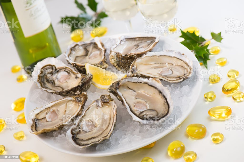 Oysters on ice and with a piece of lemon and wine stock photo