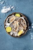istock Oysters on ice, overhead shot on a slate, with lemon and lime 1220103504