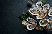 Oysters with ice and lemon on black stone background. Seafood. Top view. Free copy space.