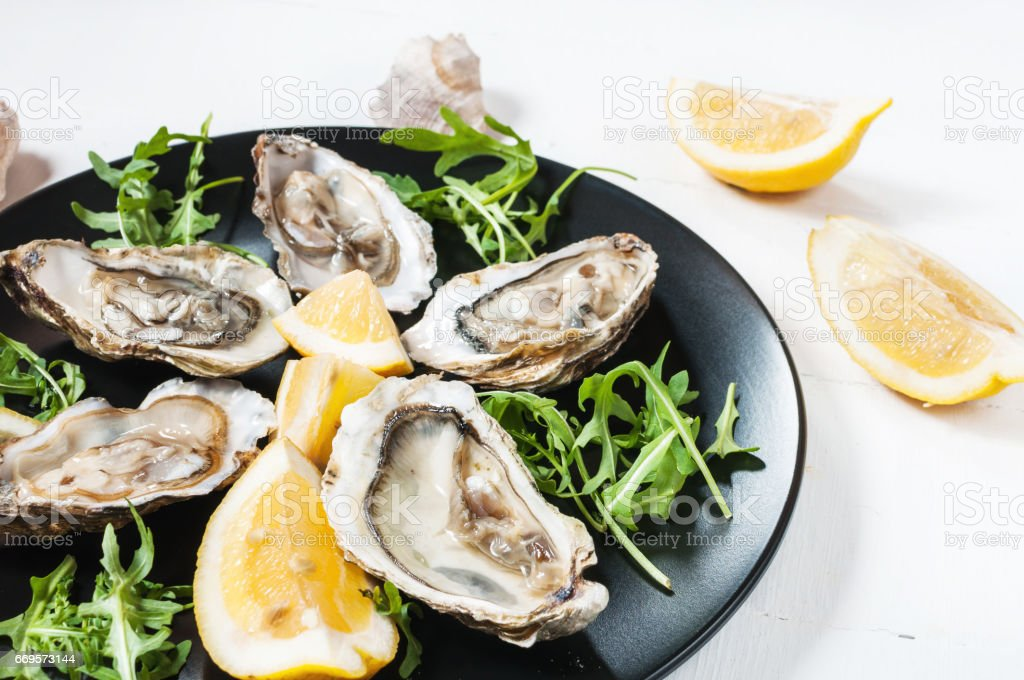 Oysters with lemon fruit on a black plate stock photo
