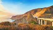 Landscape stock photograph of the curvy Pacific Coast Highway and bridge at Big Sur, California, USA, during sunset.