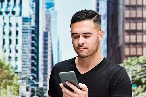 Pacific islander ethnicity male standing wearing shirt and using mobile phone