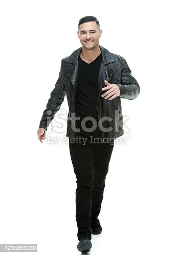 Full length of aged 20-29 years old pacific islander ethnicity young male walking in front of white background wearing jeans who is laughing