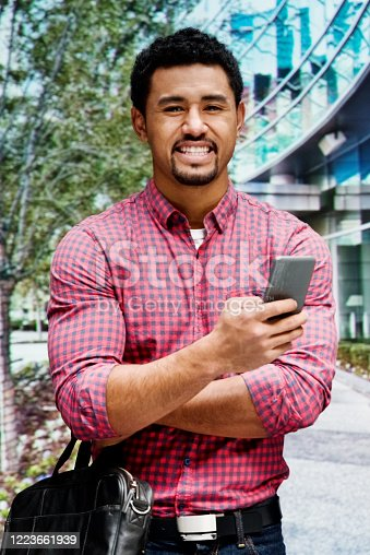 One person of aged 20-29 years old with black hair pacific islander ethnicity young male who is outdoors wearing jeans who is laughing and holding briefcase and using mobile phone