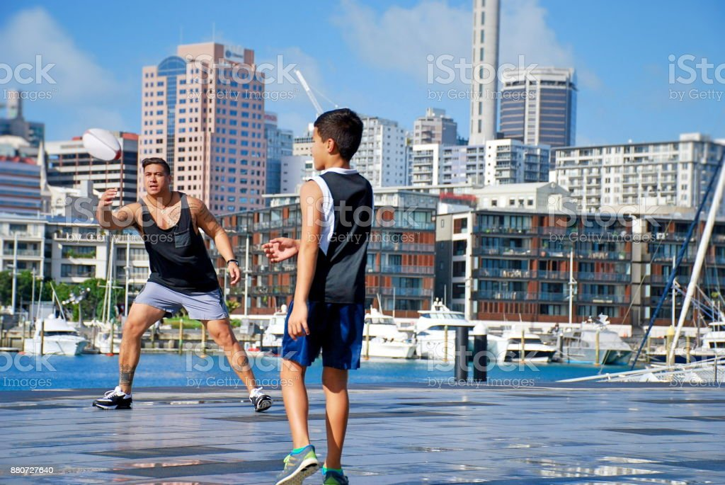 Pacific Islander Father and Son Playing Ball in Urban Cityscape Scene stock photo