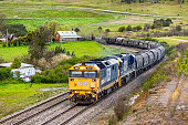 Pacific National bulk grain train rounding bend in rural landscape