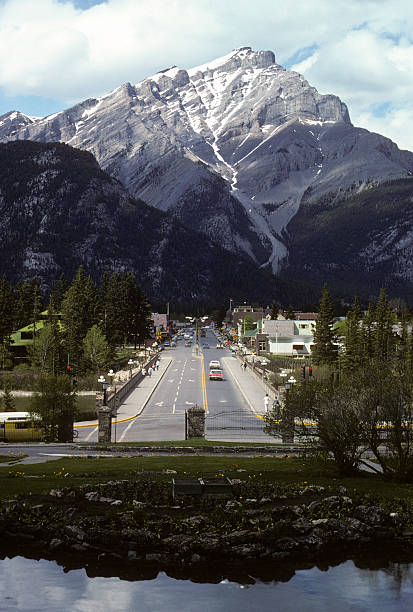 Pacific Northwest mountain town, circa 1975 Main street of a Pacific Northwest mountain town, with period cars and dress visible in the distance. Banff. Photo taken in 1975. hearkencreative stock pictures, royalty-free photos & images