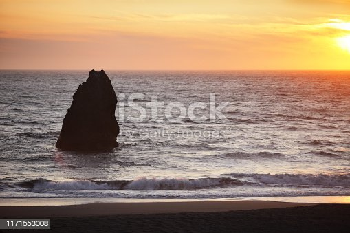 A single stack rock protrudes from Pacific coastal surf, in silhouette, with an orange and yellow sunset sky in the background and small surf running up onto a dark beach.