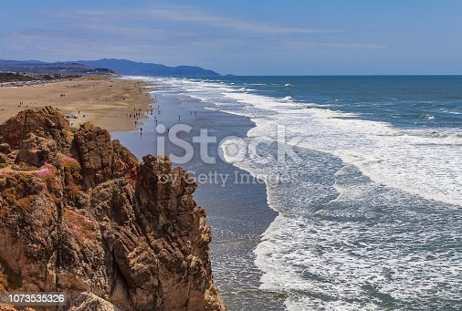 Pacific Ocean waves crashing on the sandy Ocean Beach in San Francisco with a rugged cliff covered in flowers in the background