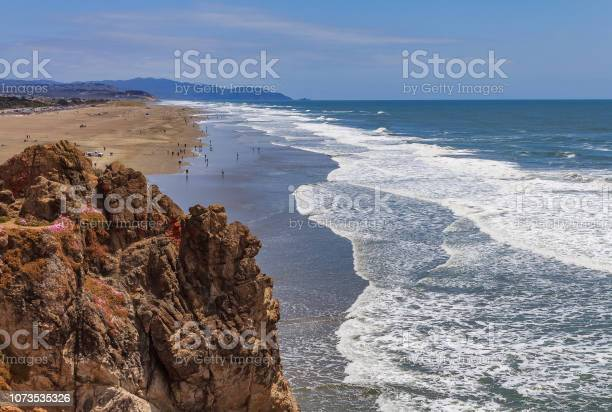 Photo of Pacific Ocean waves crashing on the sandy Ocean Beach in San Francisco with a rugged cliff in the background