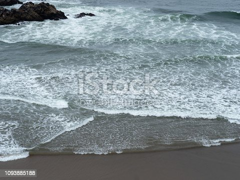 Pacific Ocean waves rolling onto a quick beach on a cold grey day