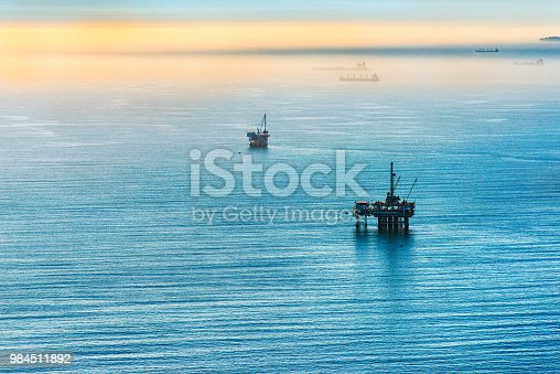 Two offshore platforms drilling for oil off the coast of Los Angeles, California with the silhouettes of several oil tankers in the background fog.