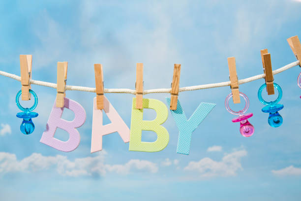 pacifiers and baby letters hanging on a clothesline - its a girl stock photos and pictures