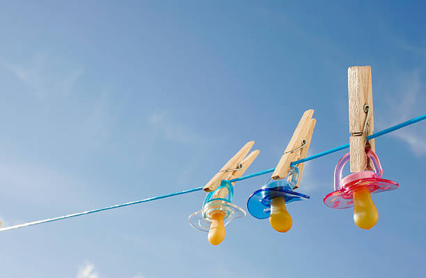 pacifiers in clothes line - triplets stock photos and pictures