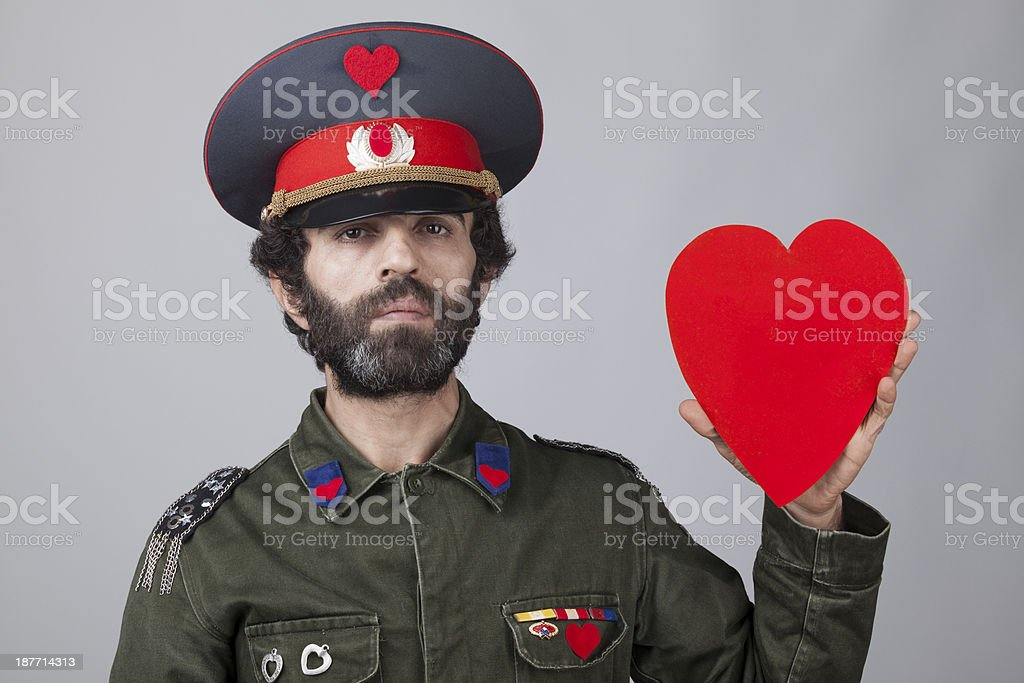 Pacifist general in military officer uniform holding heart shape stock photo
