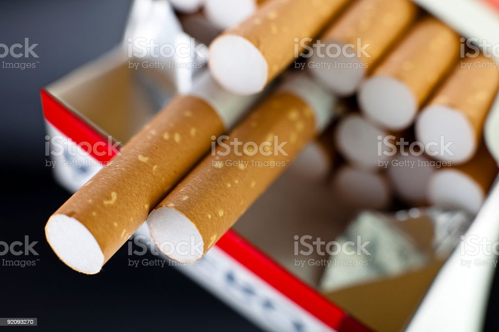 Pack of Cigarettes with two hanging over pack stock photo