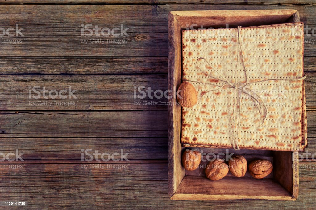 Pack of matzah or matza on a vintage wood background with copy space...