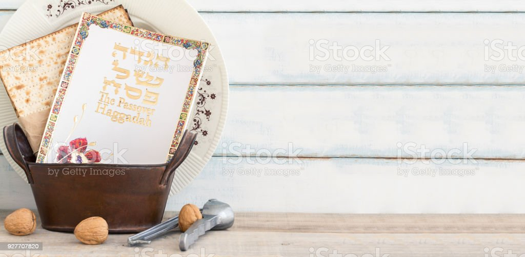 Pack of matzah or matza, Passover Haggadah and white passover seder plate on a vintage wood background. stock photo