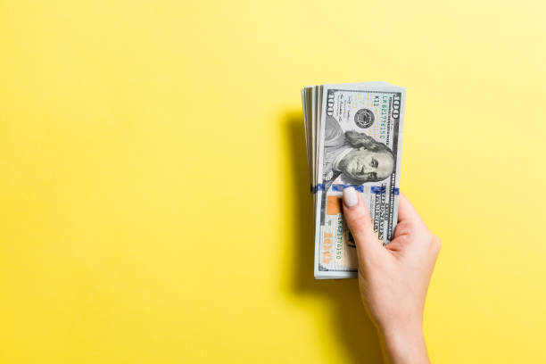 Pack of one hundred dollar bills in femle hands with copy space. Top view of money saving concept on colorful background stock photo