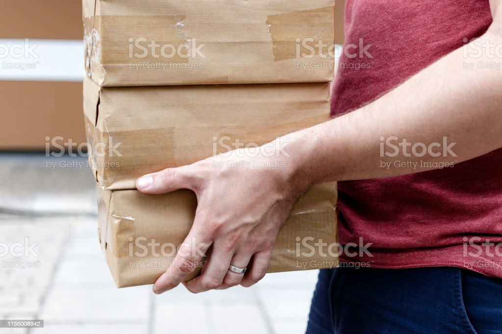 Package delivery. Delivery man is holding packaging or cardboard...