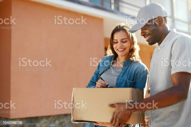 Package delivery man courier delivering box to woman at home picture id1045266726?b=1&k=6&m=1045266726&s=612x612&h=ivkia24u6vqbwos djki0pszittuqnd7ghqhrceudjq=