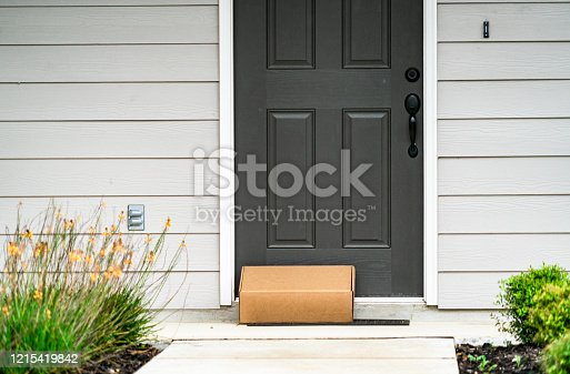 Package Delivery on Doorstep during Covid-19 pandemic , perfect suburb home with grey front door and cardboard box on door step