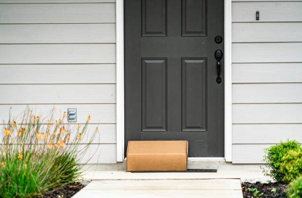 Package Delivery on Doorstep during Covid-19 Lockdown Package Delivery on Doorstep during Covid-19 pandemic , perfect suburb home with grey front door and cardboard box on door step package stock pictures, royalty-free photos & images
