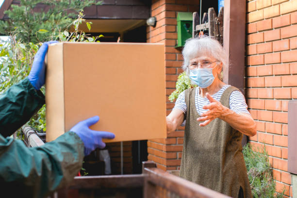 package delivery to senior woman during pandemic stock photo
