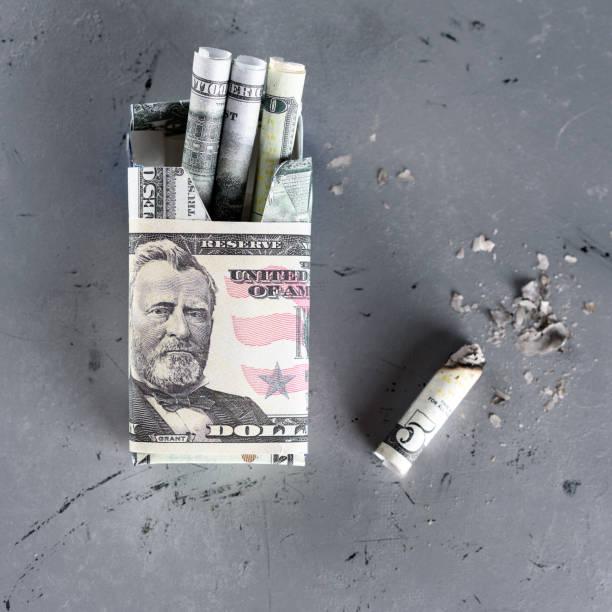 packung zigaretten gefüllt mit papiergeld dollar-banknote und zigarettenstummel. - geld schön verpacken stock-fotos und bilder