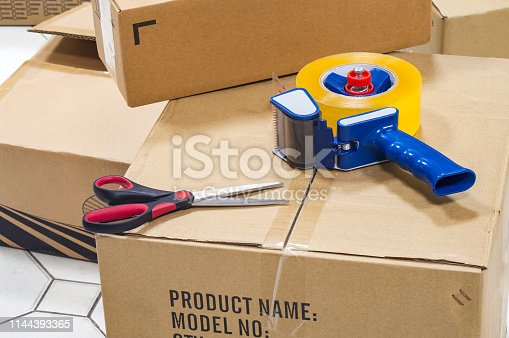 Packing tape dispenser, scissors on the cardboard box.
