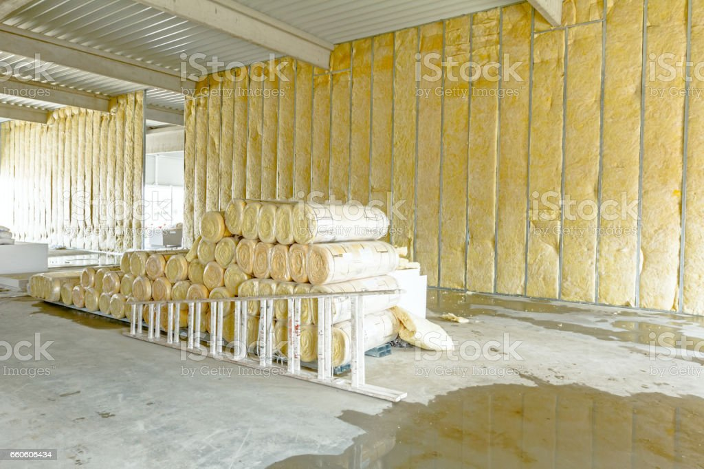 Package of thermal insulation material, rock wool is wrapped in foil. Used wooden ladder royalty-free stock photo