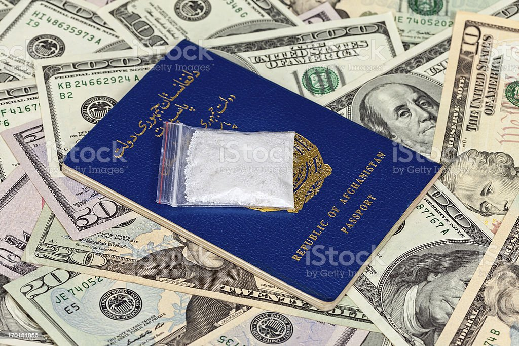 Package with drug over the Afghan passport and U.S. dollars royalty-free stock photo