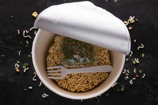 packende instant-nudeln auf schwarzem hintergrund - schnelle suppen stock-fotos und bilder