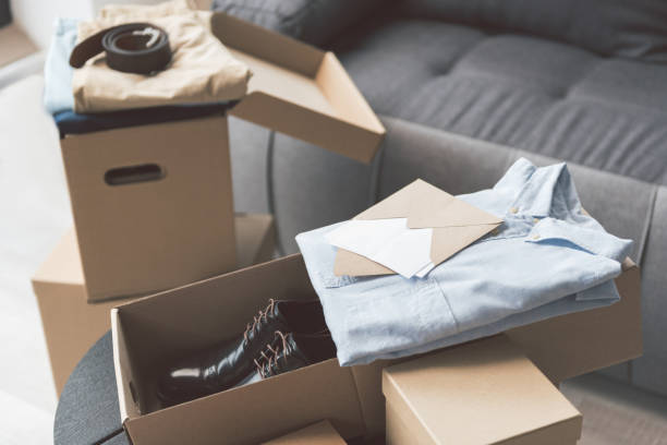 Packages with shirts locating in apartment Different opened poat boxes with new clothes and footwear situating in cozy living room. Envelope with letter is on them clothes in box stock pictures, royalty-free photos & images