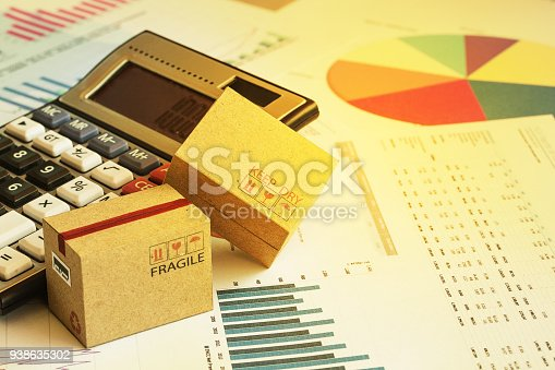 Packaging cardboard boxes with calculator and this type of financial charts include stacks of bar compare between the expansion of export business and increase the rate of goods each year.