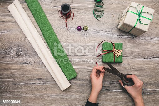 istock Packaging christmas present boxes . Top view of hands on white wood table with fir tree branches, decoration 859005984