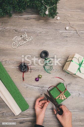 istock Packaging christmas present boxes . Top view of hands on white wood table with fir tree branches, decoration 859006560