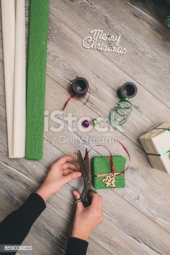 istock Packaging christmas present boxes . Top view of hands on white wood table with fir tree branches, decoration 859006820