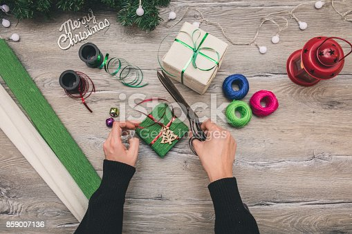 istock Packaging christmas present boxes . Top view of hands on white wood table with fir tree branches, decoration 859007136